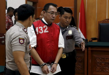 Indonesian policemen guards drug dealer Wong Chi Ping as he arrives at a court room for his trial in West Jakarta district court