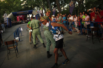 Spanish runner Juan Manuel Cortes is congratulated by a Spanish Legionnaire as he crosses the finish line to win the XVII 101km competition in Ronda