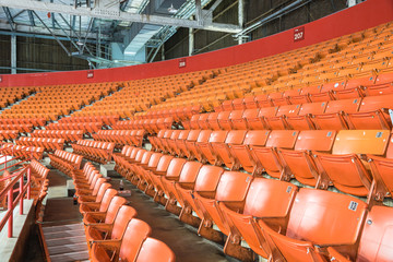 Rows of multilevel empty orange metal grandstand seats with number at an indoor sport stadium in Texas, America. Seamless pattern of stadium/arena chairs on main stand for sport concept background.