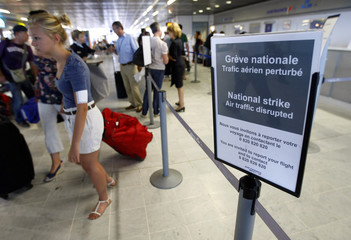 Passengers queue at an airline check-in counter at Nice airport after several flights were cancelled due to a strike by French air traffic controllers