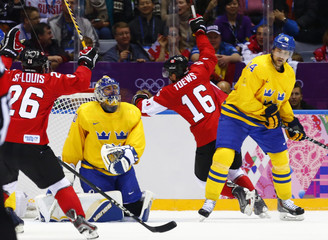 Canada's Toews and St-Louis celebrate Toews' goal against Sweden's goalie Lundqvist as Sweden's Berglund reacts during the first period of the men's ice hockey gold medal game at the 2014 Sochi Winter Olympic Games