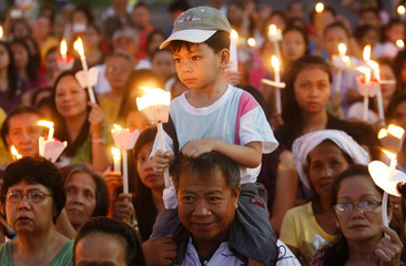 Catholics hold candles as they join in the procession to celebrate the Feast of the Resurrection at the dawn of Easter Sunday, outside a church in Manila