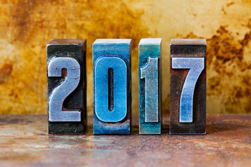 2017 year postcard. Colorful letterpress digits on rusty metal background. Retro style design xmas poster. Shallow depth field.