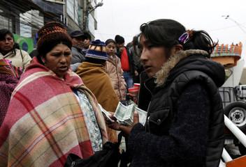 A woman sells replicas of U.S. hundred dollar bills at a market in El Alto