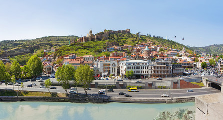 Panorama view of Tbilisi, capital of Georgia country. Landmarks - Narikala fortress, cable road above tiled roofs, Meidani square.