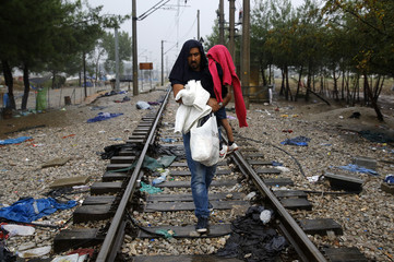 A Syrian refugee man carries his child as he crosses the border from Greece into Macedonia