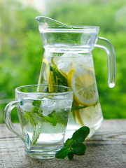 Drink with lemon and mint in a glass jug