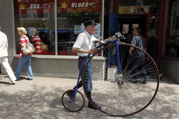 A man walks an old fashioned bicycle down the street at the Watch City Festival celebrating Steampunk in Waltham