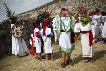 Dancers take photos as they welcome the spring equinox next to the Pyramid of the Sun in the pre-hispanic city of Teotihuacan, on the outskirts of Mexico City