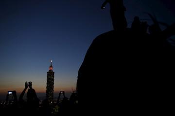 People take photo as Taiwan's landmark building Taipei 101 is seen during sunset in Taipei, Taiwan