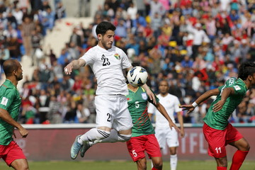Jordan's Yousef Mohammad (C) jumps for the ball against Bangladesh's players in Amman