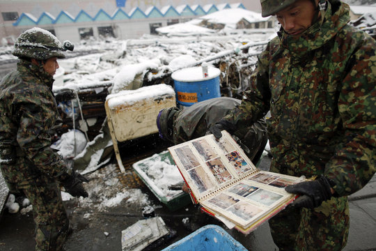 A Japan Self Defense Force officer retrieves photo album from the ruins of the residential area of Otsuchi as heavy snow falls, days after the area was devastated by a magnitude 9.0 earthquake and tsunami