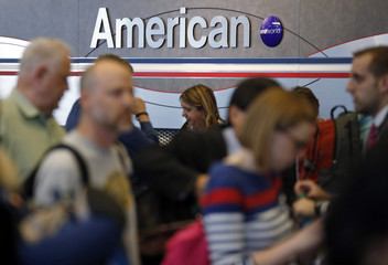 Travelers line up at an American Airlines ticket counter at O'Hare Airport in Chicago