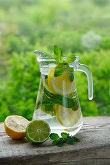 A cold drink made of lemon, lime and mint in a glass jug