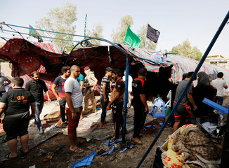 People gather at the site of a suicide bomb attack in the city's northern al-Shaab district in Baghdad