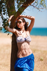 Lifestyle summer portrait of girl relaxed and getting sunbathe, leaning on a tree on the background of dry grass,wearing bright bikinis and blue long skirt,stylish vintage sunglasses.