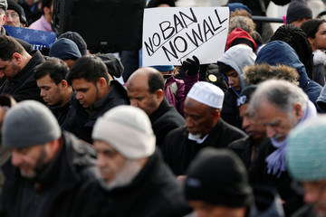 People participate in prayers during an interfaith event and the Jummah prayer outside Terminal 4 at John F. Kennedy Airport in New York