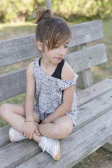Girl sitting on a wooden bench