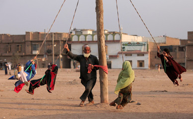 A man spins children on a home made merry-go-round in a vacant lot in Peshawar