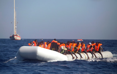 A dinghy overcrowded by African migrants is seen drifting off the Libyan coast as the Spanish rescue vessel Astral, operated by the NGO Proactiva sails in the background, in Mediterranean Sea