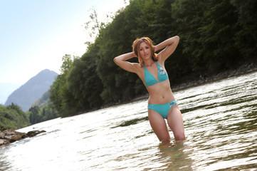 Frau im Bikini badend am Strand im Wasser