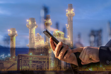 Double exposure of businessman checking oil refinery industry plant by smart phone in the night as Energy and Technology concept