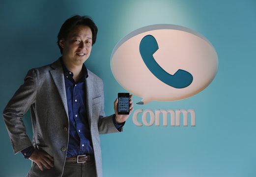 """Japanese gaming firm DeNA Co's President Moriyasu poses next to a logo of his company's icon of a free communication app """"comm"""", at the company headquarters in Tokyo"""