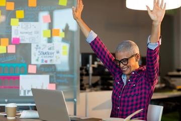Creative businesswoman celebrating on desk