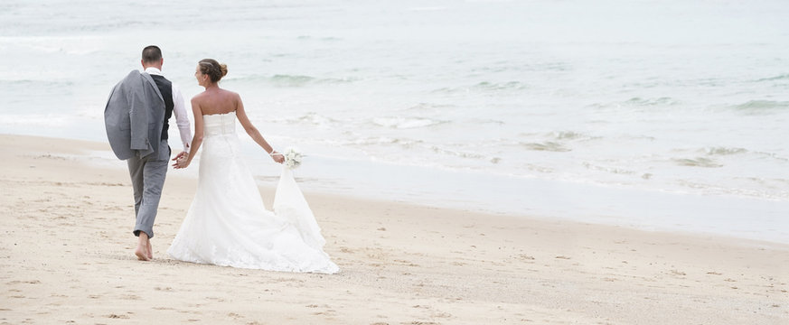 Back view of bride and groom walking on the beach