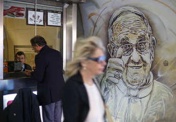 A mural by French street artist Christian Guemy, also known as C215, which depicts Pope Francis giving the thumbs-up sign, is seen in a subway station in downtown Rome