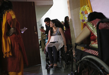 A competitor is given instructions by an organiser backstage during Miss Wheelchair India, in Mumbai