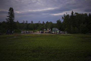Beekeeper, or apiarist, moves beehives onto a truck to be transferred to another crop after they completed pollinating a blueberry field near Jonesboro, Maine