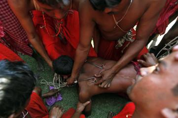 "Metal hooks are attached to a Hindu devotee during ""Chadak"" rituals at Krishanadevpur village"