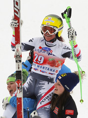 Fischbacher of Austria is carried by her compatriots Fenninger and Schmidhofer after winning the women's FIS Alpine Skiing World Cup Downhill race the Swiss resort of Crans Montana