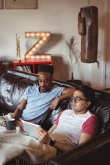 Gay couple using digital tablet while sitting on a couch