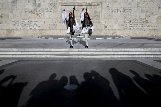 People are silhouetted as Greek Presidential guards conduct their ceremonial march in front of the Tomb of the Unknown Soldier in Athens