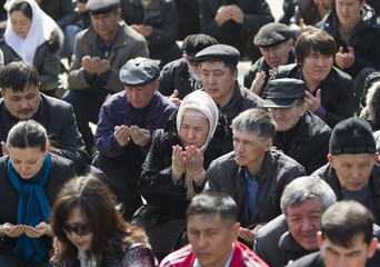 People pray during an opposition rally in Almaty