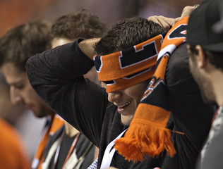 NHL Vancouver Canucks' Bieksa puts a BC Lions scarf over his eyes while attending their CFL football game against the Calgary Stampeders in Vancouver