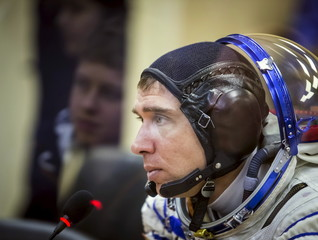 Cosmonaut Sergei Volkov of Russia speaks with his family members reflected on a glass wall between them after donning his space suit at the Baikonur cosmodrome
