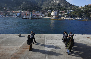 Relatives of victims pose for a picture in front of the capsized cruise liner Costa Concordia on the deck of Giglio harbour