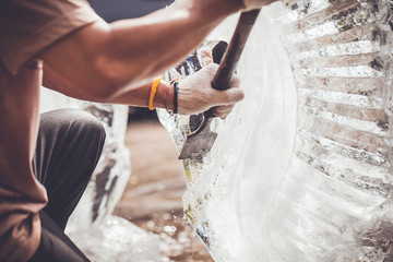 man is carving the ice sculpture for wedding