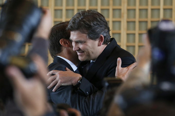 Outgoing French Economy Minister Montebourg embraces newly-named Economy Minister Macron during the official handover ceremony at the Bercy Finance Ministry in Paris
