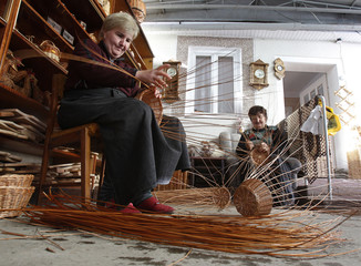Women weave baskets out of a willow twigs in the village of Iza