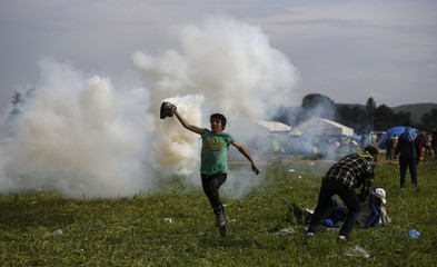 A protesting migrant runs with a teargas canister to throw it over a border fence towards Macedonian police during clashes at the Greek-Macedonian border near Idomeni