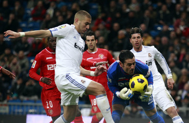 Real Madrid's Benzema tries to score past Sevilla's goalkeeper Palop  during their first division soccer match at Santiago Bernabeu stadium in Madrid