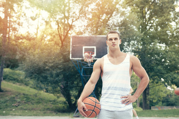 Young attractive player standing on basketball court holding ball and posing. Sport outdoors theme.