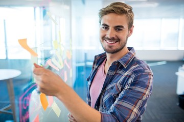 Smiling man touching sticky note on glass wall in office