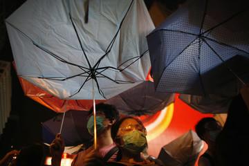 Pro-democracy protesters hold umbrellas as they face policemen at the Mongkok shopping district of Hong Kong