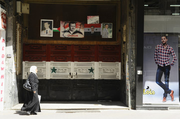 A woman walks past a metal gate painted with the Syrian national flag colours and displaying pictures of Syrian President Assad in Damascus