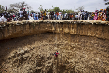 People watch a man descend into a large former well during a traditional ceremony in the village of Ndande